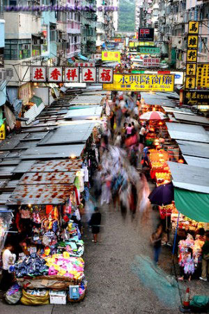 Backpackers Bartering in a Hong Kong Street Market