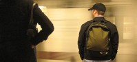 Guy in hat wearing a backpack in the subway