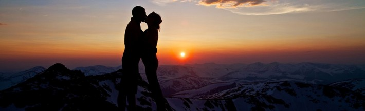 Couple kissing over a mountain sunset